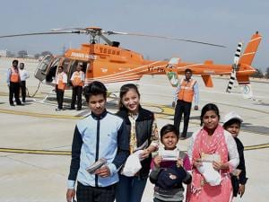 Passengers showing their tickets before flying in a Pawan Hans helicopter