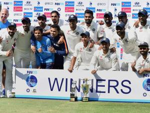 Indian cricket team and support staff pose with the winner's trophy after defeating Bangladesh