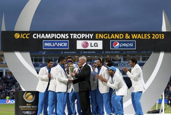 India's captain Mahendra Singh Dohni, second left, receives the trophy from ICC President Alan Isaac after India won the ICC Champions Trophy Final cricket match by beating England at Edgbaston cricket ground, Birmingham