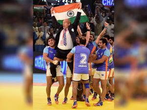 Indian players lift their coach as they celebrate