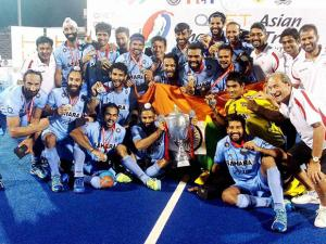 Indian hockey players pose with the Asian Champions Trophy after they beat Pakistan in the final