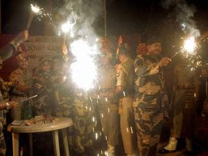 Indian Border Security Force soldiers light candles and crackers during Diwali celebrations