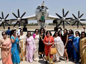 Family members of Navy personnel pose for a photograph in front of India's long range maritime patrol aircraft, TU-142M