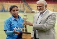Mithali Raj receiving trophy from former cricketer Brijesh Patel