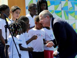 International Olympic Committee President Thomas Bach, right, visits with members of a children's choir