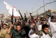 Iraqi Shiite tribal fighters raise their weapons