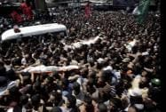 Palestinian mourners carry the body of three senior commanders of the Hamas military wing