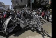 Palestinians move the wreckage of a vehicle following an Israeli airstrike off