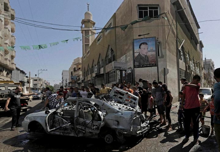 Palestinians, gather, around, wreckage, vehicle, Israeli, airstrike, Gaza City, everal, Palestinians, killed, several, wounded, airstrike, car, according, Gaza, health official, Ashraf al-Kidra