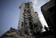Palestinians inspect the damage to the Italian Complex following several late night Israeli airstrikes