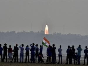 People watch as as a rocket from  Space agency Indian Space Research Organisation (ISRO) takes off