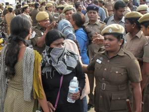Policemen detain students who were holding a protest demanding a permanent solution for holding the Jallikattu