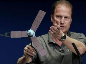 Rick Nybakken, Juno project manager, holds a model of the Juno spacecraft while talking