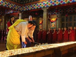 In this photo provided by Royal Kingdom of Bhutan, Kate, Duchess of Cambridge, is helped by Bhutan's King, Jigme Khesar Namgyel Wangchuk, as she lights up an oil lamp in Thimphu, Bhutan.