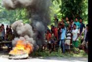Protestors block the National Highway 37 at Geleki in Kaziranga