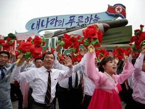 North Korean parade participants wave decorative bouquets of flowers and carry their country's national flag as they march with different types of models of missiles at the Kim Il Sung Square