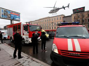 A helicopter flies over the fire trucks after an explosion at Tekhnologichesky Institut subway station in St.Petersburg