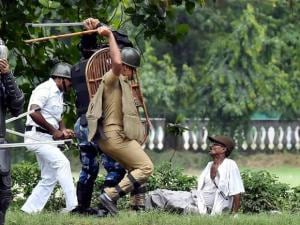 Police and RAF personnel lathicharge on an activist of Left Front affiliated peasants organisation