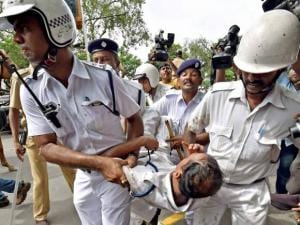 Policemen carry a colleague injured in clash with  activists of Left Front affiliated peasants organisations