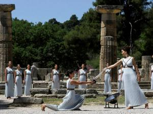 Dancers dressed as priestesses hand over the Olympic flame during the ceremonial lighting of the Olympic flame in Ancient Olympia, Greece