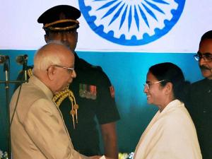 est Bengal Governor Keshari Nath Tripathy greets West Bengal Chief Minister Mamata Banerjee after administrating the oath of secrecy during the swearing-in ceremony