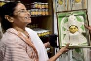 Mamata Banerjee is presented a portrait of Goddess Durga