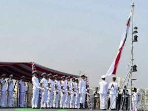 Naval  officers hoisting the flag during the commissioning of naval warship INS Kochi