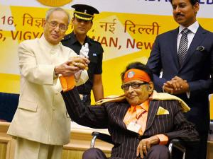 Veteran actor Manoj Kumar presenting a memento to President Pranab Mukherjee while receiving Dadasaheb Phalke Award from him at the 63rd National Film Awards 2015 function in New Delhi