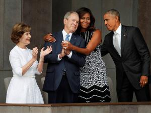 Michelle Obama, hugs former President George W. Bush, Barack Obama and former first lady Laura Bush walk on stage