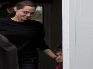 Angelina Jolie, whom the United Nations' refugee agency has appointed a special envoy holds a child during her visit at the port of Piraeus near Athens