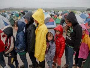 Children wait in line for food handouts during a rainfall at the northern Greek border station of Idomeni