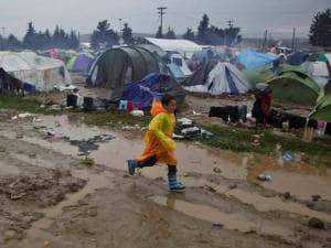 Migrant child wearing a rain poncho runs  at the Greek border camp near Idomeni