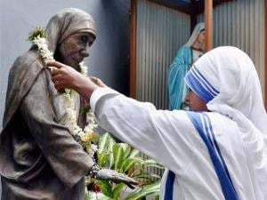 A nun offers garland to the statue of Mother Teresa