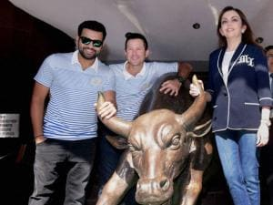 Mumbai Indians owner Nita Ambani, head coach Ricky Ponting and captain Rohit Sharma poses with the bronze statue of a bull outside the Mumbai Stock Exchange (MSE) building after attending Opening Bell Ring