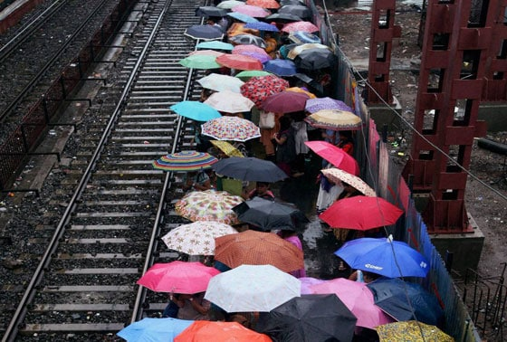 People using umbrellas during rains at Borivali railway platform in Mumbai on Monday