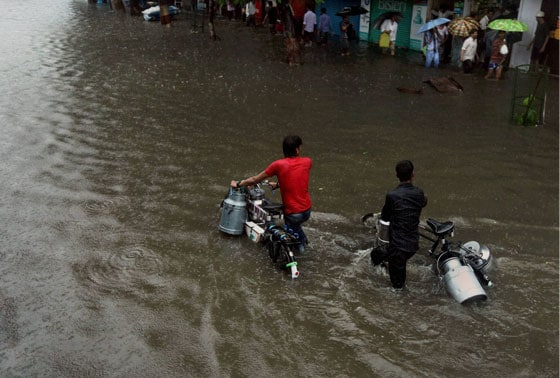 Two milk vendors wade through a flooded road at Dadar as it rains in Mumbai on Monday