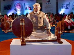 Narendra Modi works at a charkha