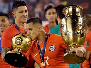 Alexis Sanchez kisses his trophy along while holding the championship trophy after the Copa America
