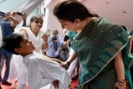 Smriti Irani interacts with a school boy performing a Yogasana