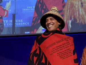 President Barack Obama smiles as he wears a blanket