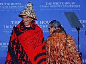 President Barack Obama smiles as he wears a ceremonial blanket and hat given to him by Brian Cladoosby President of National Congress of American Indians