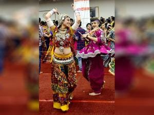 A Girl in traditional dress plays dandia during the navratri celebration