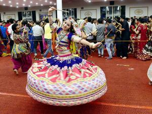 A Girl in traditional dress plays dandia during the navratri celebration in Bengaluru