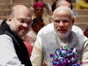 Prime Minister Narendra Modi being greeted by BJP president Amit Shah at a meeting of ruling National Democratic Alliance MP's
