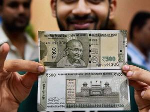 A youth shows new currency note of Rs 500 which is ready to float