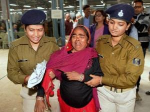 Security women take away a woman who broke into tears during Chief Minister's Janta Ka Darbar program in Patna