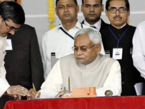 Nitish Kumar signing the register after taking oath as the Chief Minister of Bihar