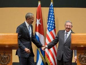 President Barack Obama and Cuban President Raul Castro hold hands on stage at the conclusion of their joint news conference at the Palace of the Revolution