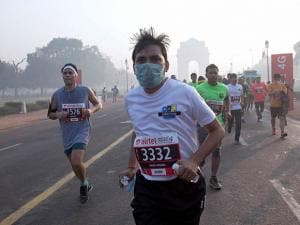 Participants run as the India Gate monument is seen