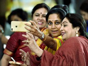 BJP MP's Kirron Kher, Meenakshi Lekhi with NCP MP Supriya Sule take selfie during a cultural evening